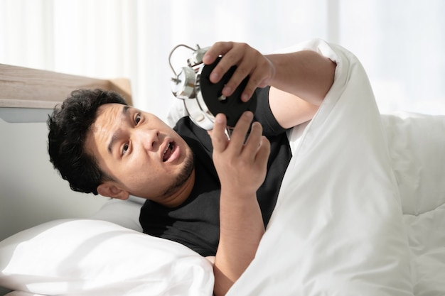 Homem asiático com rosto chocado depois de acordar tarde e perder a consulta Foto Premium