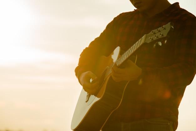 Homem asiático com violão durante um pôr do sol Foto gratuita