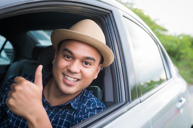 Homem asiático considerável novo que conduz o carro que mostra o polegar acima. Foto Premium