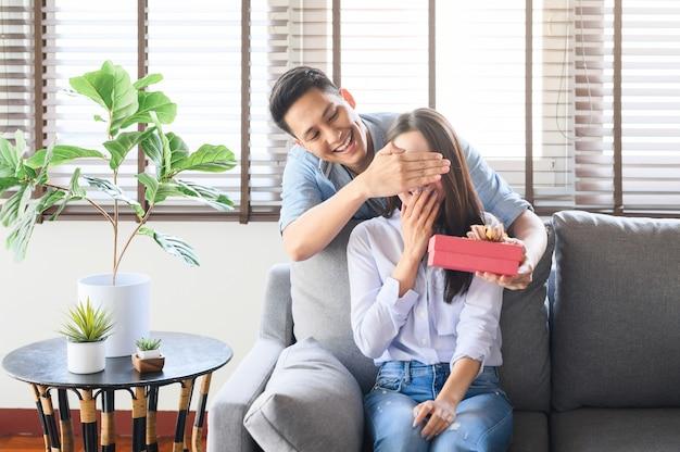 Homem asiático dando uma caixa de presente presente para surpreender sua namorada em casa Foto Premium