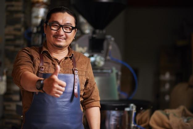 Homem asiático de meia idade, posando com o polegar na frente do equipamento de torrefação de café Foto gratuita