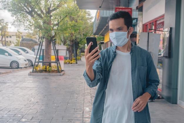 Homem asiático, desgastar, máscara facial, segurando, telefone celular, estilo vida, novo, normal, social, distanciamento Foto Premium