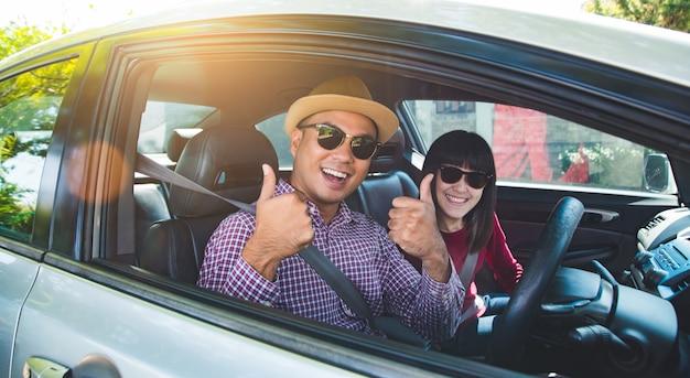 Homem asiático e mulher dos pares felizes do momento que sentam-se no carro. aproveitando o conceito de viagens. Foto Premium