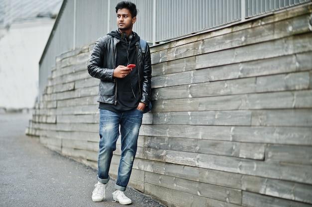 Homem asiático elegante e casual na jaqueta de couro preta, fones de ouvido com celular vermelho nas mãos colocadas na rua Foto Premium