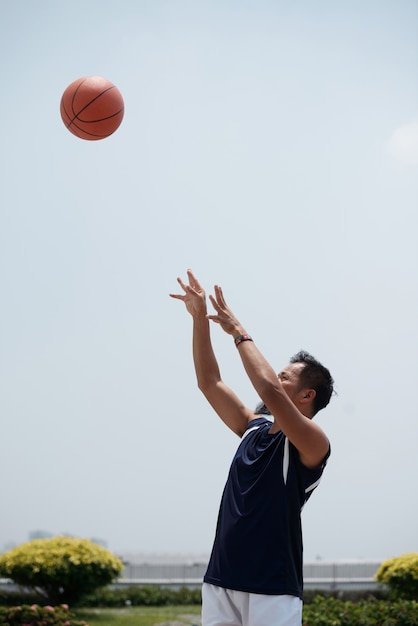 Homem asiático em pé ao ar livre no estádio e jogando beisebol no ar Foto gratuita