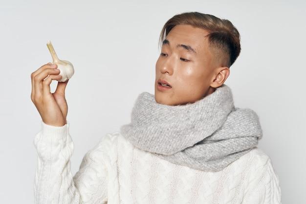 Homem asiático em roupas de inverno quente, posando em um espaço colorido espaço Foto Premium