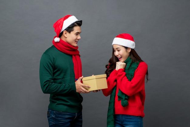 Homem asiático em traje de natal surpreender sua namorada com presente Foto Premium