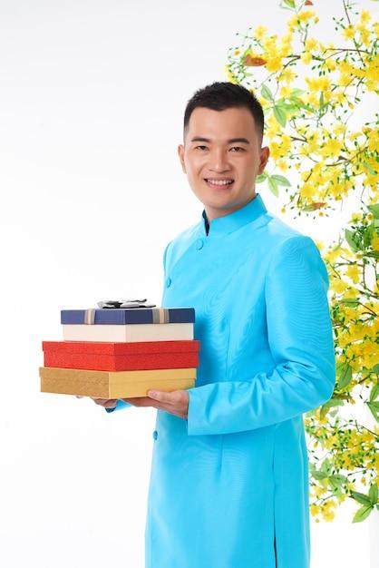Homem asiático em traje tradicional segurando caixas de presente para sua família Foto gratuita