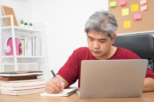 Homem asiático estudando novas habilidades da internet em casa Foto Premium