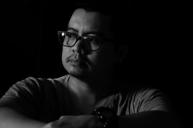 Homem asiático no escuro olhando pela janela parece triste humor Foto Premium