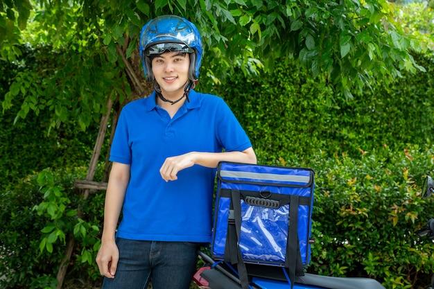 Homem asiático novo com caixa da entrega, motocicleta que entrega o conceito do serviço expresso do alimento. Foto Premium