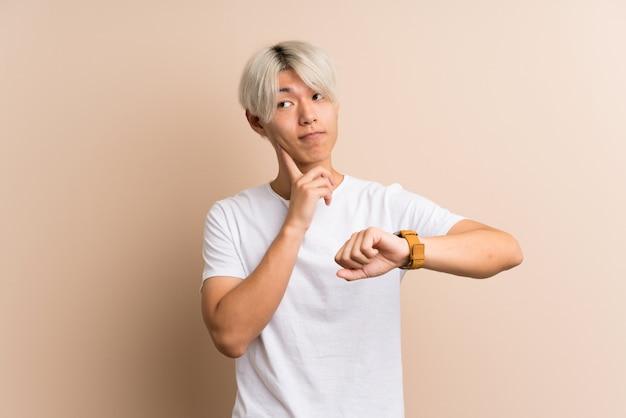 Homem asiático novo com relógio de pulso e pensando uma ideia Foto Premium
