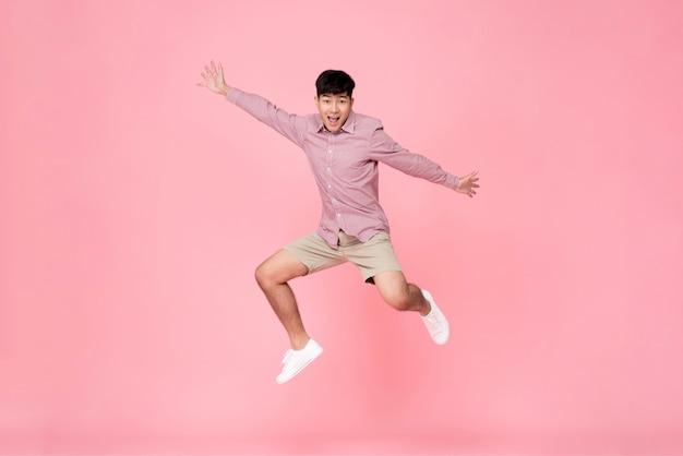 Homem asiático novo feliz energético que salta Foto Premium