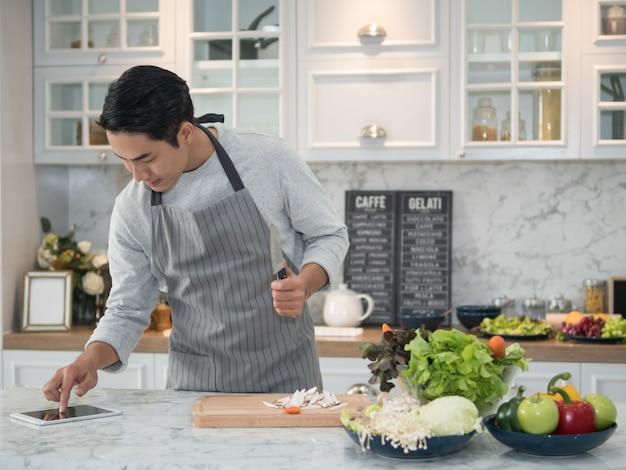 Homem asiático novo que olha a receita na tabuleta digital e que cozinha o alimento saudável na cozinha em casa. Foto Premium