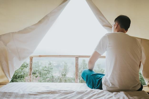 Homem asiático olhando a vista para a montanha da tenda em vez do sol Foto Premium