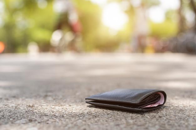 Homem asiático perder carteira preta na estrada em atração turística Foto Premium