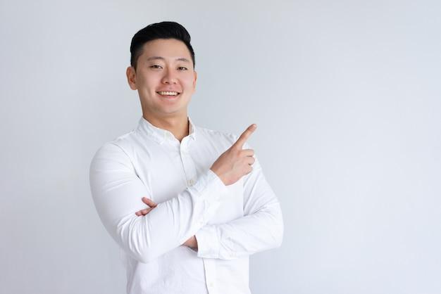 Homem asiático positivo, apontando o dedo de lado Foto gratuita