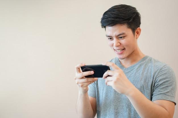 Homem asiático que joga aplicação de jogo on-line com a sensação de entusiasmo no tempo de relaxamento Foto Premium