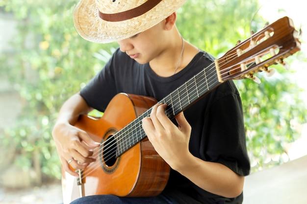 Homem asiático que joga uma guitarra clássica na natureza. Foto Premium