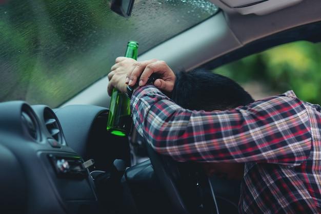 Homem asiático segura uma garrafa de cerveja enquanto está dirigindo um carro Foto gratuita