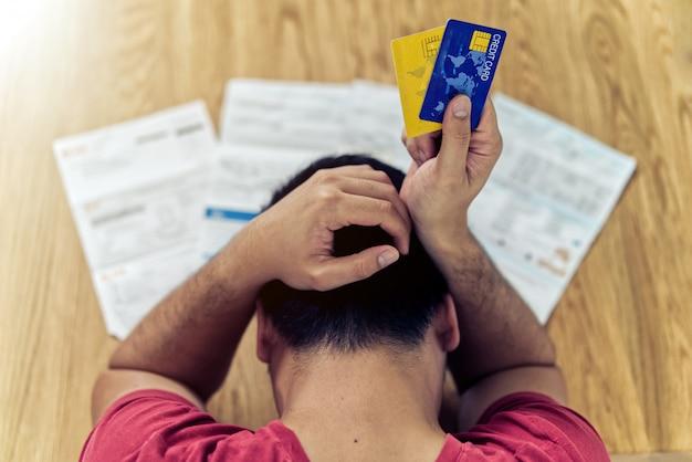 Homem asiático segurando cartões de crédito e pensando em encontrar dinheiro para pagar a dívida de cartão de crédito e todas as contas Foto Premium
