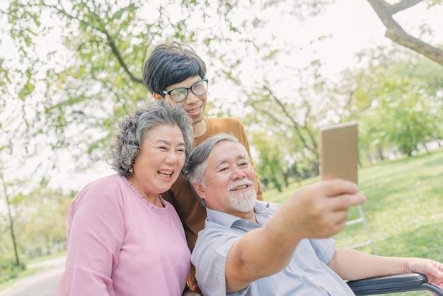 Homem asiático sênior usando smartphone para selfie com sua família Foto Premium