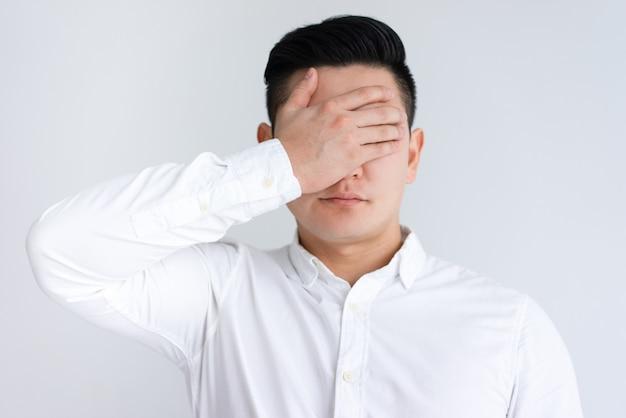 Homem asiático sério, cobrindo os olhos com a mão Foto gratuita