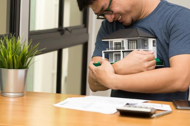Homem asiático sorrindo e abraçando uma casa de sonho e calcular para comprar uma casa sonhando com seu futuro Foto Premium
