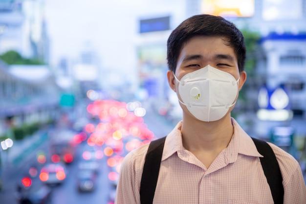Homem asiático sorrindo por trás da máscara protetora médica no novo conceito de estilo de vida normal. Foto Premium