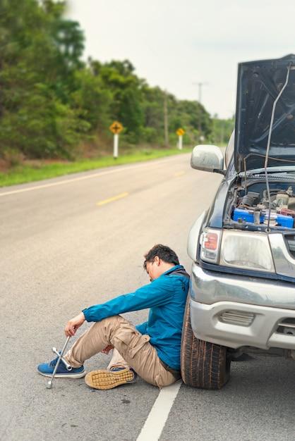 Homem asiático tendo problemas com seu carro quebrado Foto Premium