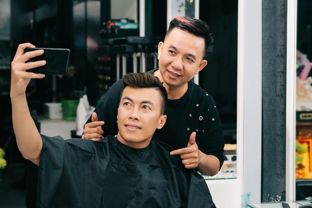 Homem asiático tomando selfie com seu cabeleireiro na barbearia Foto gratuita