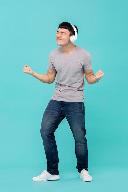Homem asiático usando fones de ouvido, ouvindo música Foto Premium