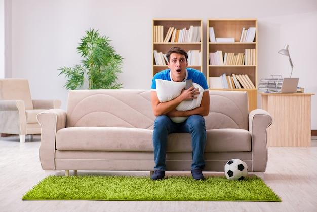 Homem assistindo futebol em casa sentado no sofá Foto Premium