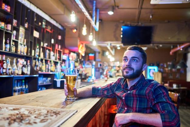 Homem assistindo tv no bar de cerveja Foto Premium