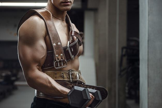 Homem atlético de poder caucasiano treinando músculos bíceps com cinto atlético. fisiculturista forte com tanquinho, abs perfeito, tríceps, peito, ombros na academia. conceito de fitness e musculação Foto Premium