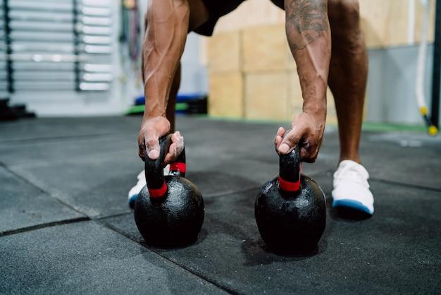 Homem atlético fazendo exercício com chaleira crossfit. Foto gratuita