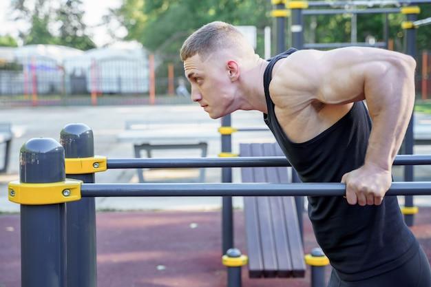 Homem atlético novo que faz push-ups em barras ao ar livre. Foto Premium