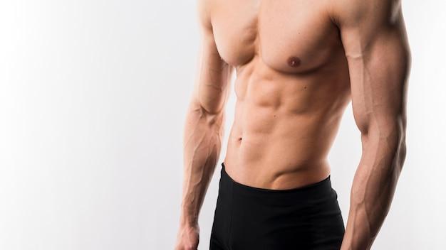 Homem atlético sem camisa, mostrando os músculos do corpo Foto gratuita