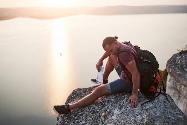 Homem atraente, apreciando a vista da paisagem de montanhas acima da superfície da água. Foto gratuita
