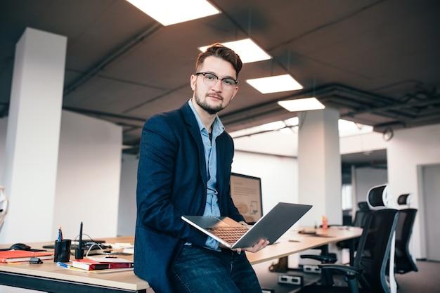 Homem atraente em glassess está sentado perto do local de trabalho no escritório. ele usa camisa azul, jaqueta escura. ele segura o laptop e olha para a câmera. Foto gratuita