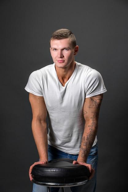 Homem atraente moda olhando para a câmera em pé com as mãos em uma cadeira Foto Premium