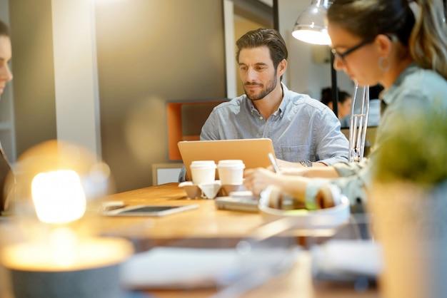 Homem atraente no laptop no espaço de trabalho co Foto Premium