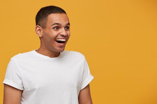Homem atraente olha de lado para algo incrível, muito feliz Foto gratuita