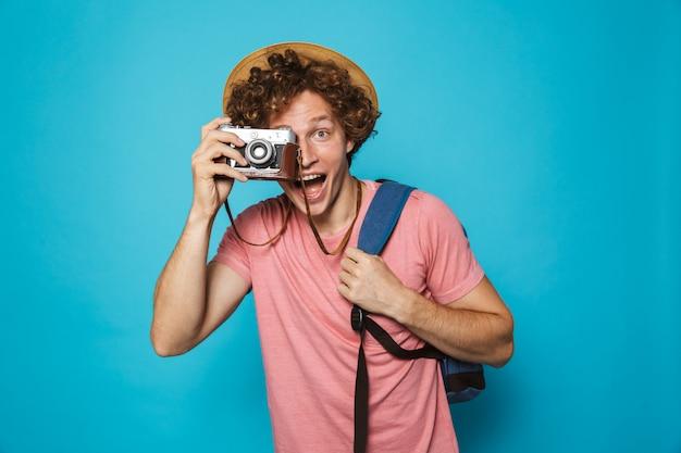 Homem atraente turista com cabelos cacheados, usando mochila e chapéu de palha fotografando na câmera retro Foto Premium