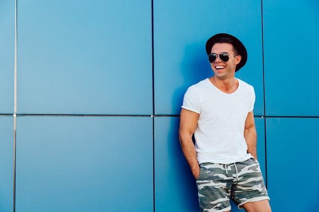 Homem atrativo novo nos óculos de sol que estão no fundo da parede azul Foto gratuita