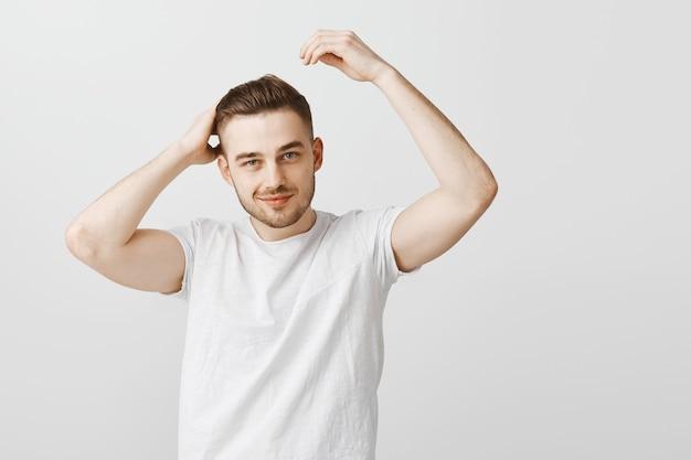 Homem atrevido e bonito satisfeito com novo corte de cabelo depois da barbearia Foto gratuita
