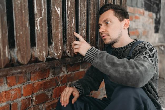 Homem autista sozinho sentado no radiador enferrujado. Foto Premium