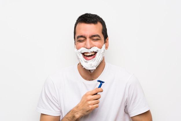 Homem barbear a barba sobre parede branca isolada, sorrindo muito Foto Premium