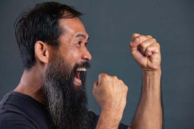 Homem barbudo agindo com raiva na parede escura Foto gratuita