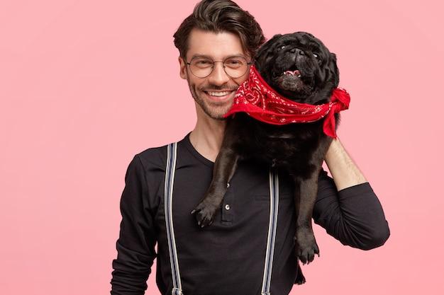 Homem barbudo alegre tem um sorriso dentuço, feliz por posar com seu cão de raça, gosta de animais de estimação, vestido com uma camisa preta da moda e suspensórios, isolado sobre a parede rosa. homem feliz com animal Foto gratuita